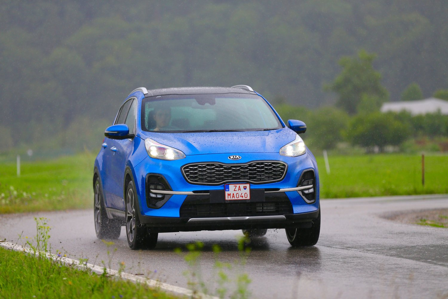 KIA Sportage Blue rainy day on road