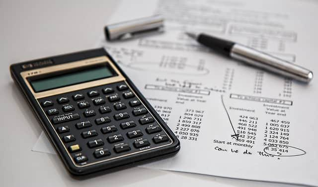 Calculator and pen on top of paper with financial information typed on it.